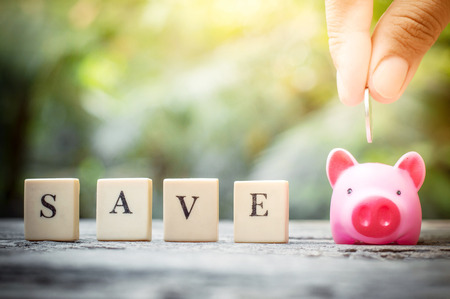 Business concept, hand putting coins in pink piggy bank for life Banco de Imagens - 123010269