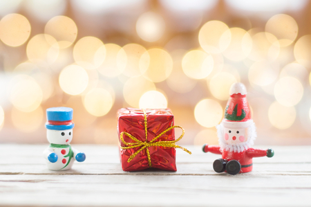 Santa Claus, Snowman doll and red gift box with shiny light for Christmas decoration background