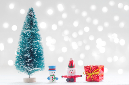 Christmas tree, Santa Claus, Snowman doll and red gift box with shiny light for Christmas decoration background