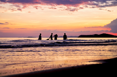 Silhouette of people playing in to the sea with dramatic sunset sky Banco de Imagens - 123010618