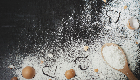 Heart of flour, flour in wooden spoon and eggshell on wooden table for baking background Banco de Imagens - 123010636