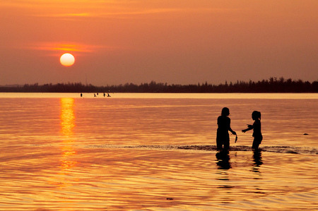 Happy children playing on the beach at sunset
