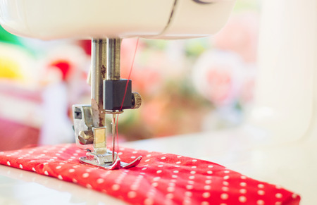 Close up of sewing machine working with red fabric Banco de Imagens