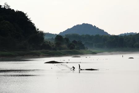 Silhouette of fisherman throwing fishing net at reservoir Banco de Imagens - 123010673