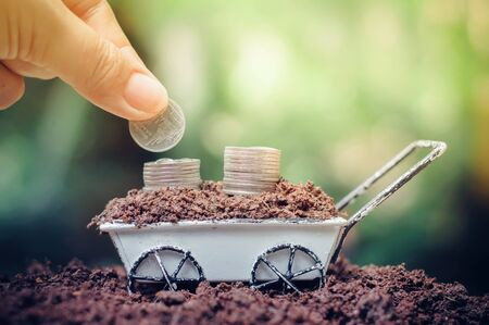 Close up of hand putting coins in stack of coins is growing up on wheel barrow for business investment or saving concept Banco de Imagens