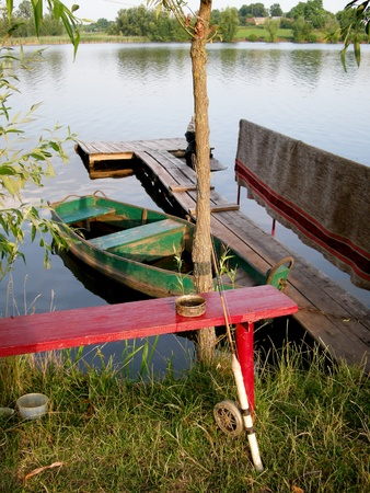 lake shore: red wooden  bench  with a fishing rod on the shore of Lake