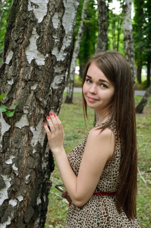 european white birch: girl standing near birch on a background of blurred trees and greenery