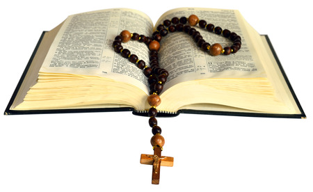 rosary beads: opened book with wooden Christian rosary on white background