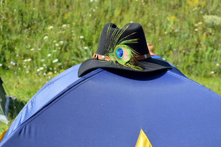 leisure wear: a black hat with a peacock feather on a blue tent Stock Photo