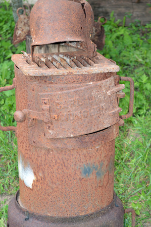 stove pipe: old rusty stove with a broken helmet on a background of green grass Stock Photo