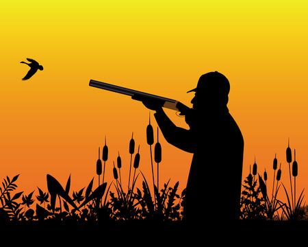 Hunter aiming a shotgun in a wild duck in the grass and reeds