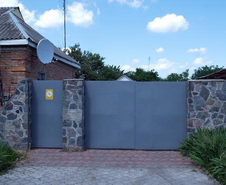 puertas de hierro: puertas de hierro antena parabólica valla de piedra Foto de archivo