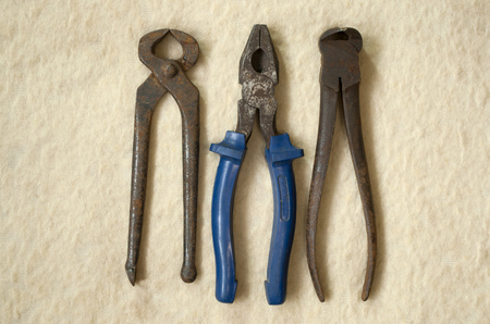 old rusty tongs and pliers on a light background