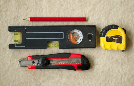 set of construction tools level roulette knife carpentry pencil on a light background