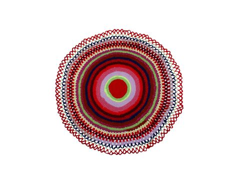 round mat knitted with colored threads on a white background