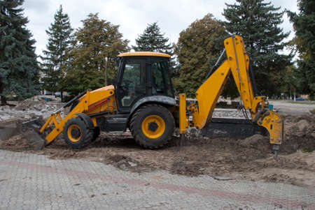 excavator stands on the ground near the foundation