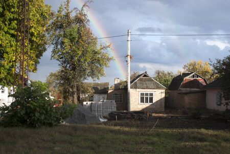 autumn rainbow behind the house and trees