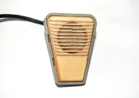 old microphone for voice with a wire on a light background