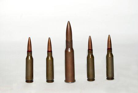 five machine gun cartridges on a light background