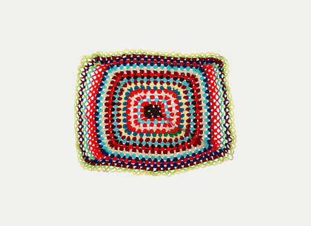 knitted foot mat with multi-colored threads on a white background