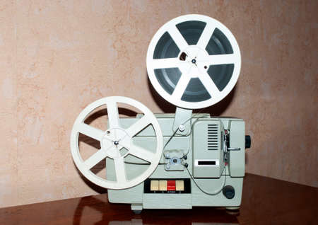 old movie projector and reels of film standing on the table