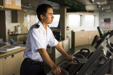 Junge chinesische Navigator Navigating sein Schiff