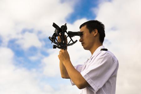 Joven china Navigator Haciendo observación del cielo con el sextante Foto de archivo