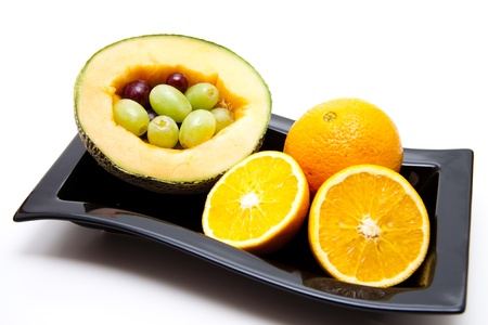 Melon half with oranges and grapes Stock Photo - 12857391