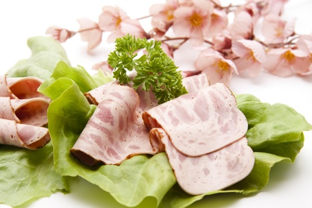 artificially: Sausage on salad leaf with flower branch Stock Photo