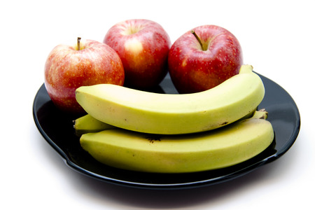 Bananas and red apples on black plate