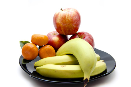 Bananas and apples with oranges on black plate Stock Photo