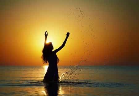 Silhouette di donna, rendendo gli spruzzi i raggi del sole che sorge. Foto orizzontale  Archivio Fotografico
