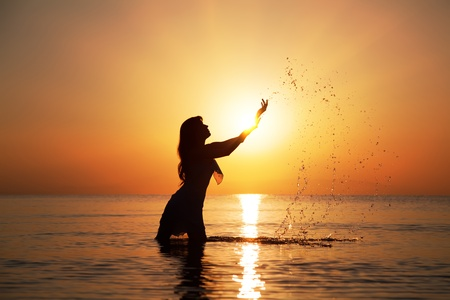 Silhouette of woman making splashes in the rays of the rising sun. Horizontal photo photo