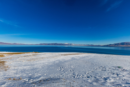 The frozen Sailimu lake with snow mountain background at Yili, Xinjiang of China