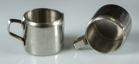 two metal nickel-plated cups on a white background.