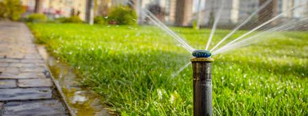 automatisch sproeisysteem dat het gazon op een achtergrond van groen gras water geeft