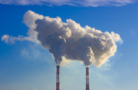 The pipe of the plant emits harmful substances into the atmosphere. Close-up on a sky background
