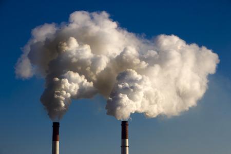 De pijp van de plant stoot schadelijke stoffen de atmosfeer in. Close-up op een hemelachtergrond