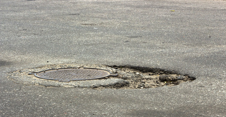 Waterfilled pothole on asphalted road. pothole on asphalt Stock Photo