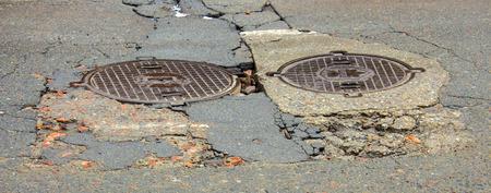 Waterfilled pothole on asphalted road Standard-Bild