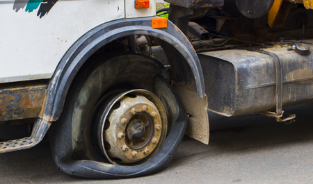 A broken front wheel, an old white truck. close up