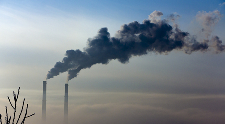 The pipe of the plant emits harmful substances into the atmosphere. Close-up on sky background