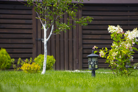 garden lamp, made in the Middle Ages, on a lawn with a juicy green grass. Stock Photo