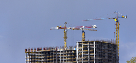 tower crane against the blue sky, the process of building a multi storey building