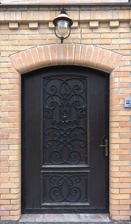 An old medieval wooden door with a studded forged iron frame