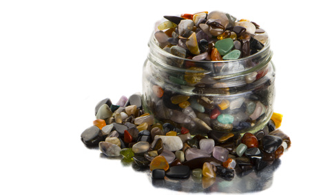 Full to the top glass jar with semiprecious stones, isolated on white background close up