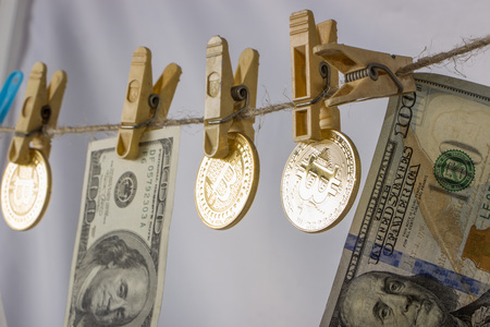 Money laundering concept. Yellow clothes peg hold Bitcoin and one hundred dollar banknotes. Stock Photo
