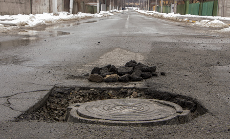 Pothole in asphalt near the sewer hatch, in the middle of the street Stok Fotoğraf