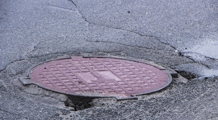 Pothole in asphalt near the sewer hatch, in the middle of the street Stock Photo