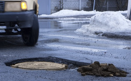The car drives past the pothole with puddles on the road
